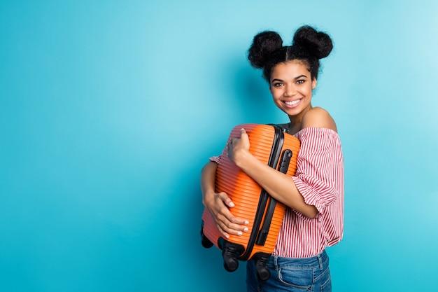 Zdjęcie profilowe śmiesznej ładnej ciemnej skóry pani trzyma dużą ciężką walizkę blisko klatki piersiowej ząbkowaną uśmiechniętą odzież podróżną w paski czerwona biała bluzka dżinsy izolowane niebieski kolor ściana