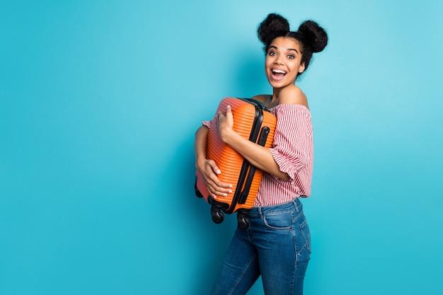 Zdjęcie profilowe śmiesznej ładnej ciemnej skóry pani trzymającej dużą ciężką walizkę cieszyć się podróżowaniem za granicę nosić czerwoną białą bluzkę z odkrytymi ramionami dżinsy izolowane niebieski kolor ściana