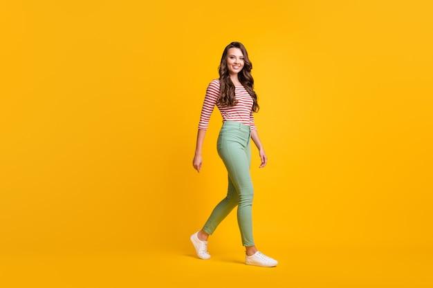 Zdjęcie profilowe z boku na całej długości ciała dziewczyny z kręconymi włosami spieszącej się uśmiechniętej na żywym żółtym kolorze tła