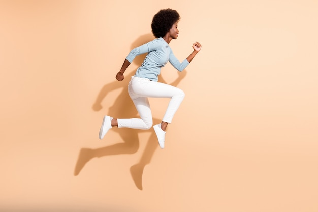 Zdjęcie profilowe z boku na całej długości ciała kręconej, ciemnoskórej dziewczyny skaczącej wysoko, biegnącej szybko, noszącej zwykłe ubrania odizolowane na beżowym tle