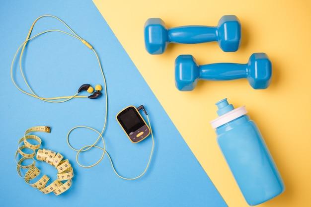 Zdjęcie przedmiotów sprawności. zawodnik, hantle, butelka wody, taśma centymetrowa na niebieskim i żółtym tle