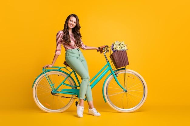 Zdjęcie przedstawiające całą długość ciała, przedstawiające ładną dziewczynę siedzącą na rowerze z koszem kwiatów uśmiechniętą na tle żywego żółtego koloru