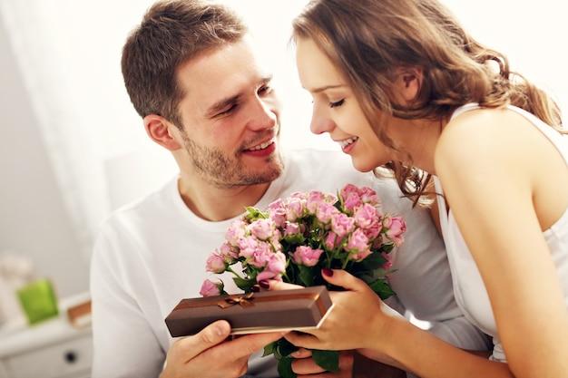 Zdjęcie przedstawiające mężczyznę dającego kwiaty i prezent kobiecie w łóżku