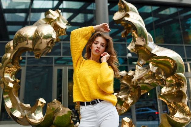 Zdjęcie przedstawiające młodą modelkę czującą wolność i pozującą na tle złotej rzeźby
