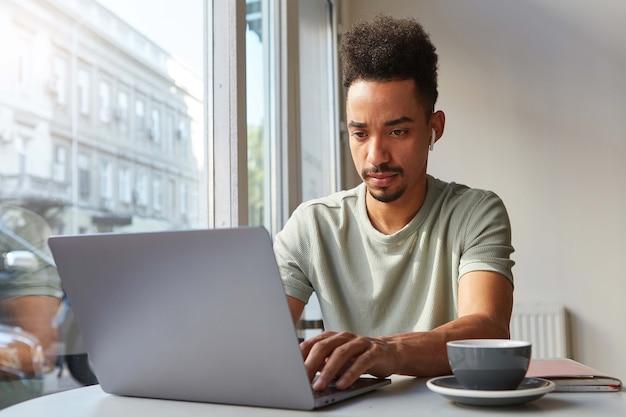 Zdjęcie przedstawiające młodego atrakcyjnego ciemnoskórego chłopca z koncentratem, pracuje przy laptopie w kawiarni, pije kawę i w zamyśleniu patrzy na monitor.