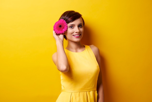 Zdjęcie przedstawiające modelkę trzymającą kwiat przy uchu