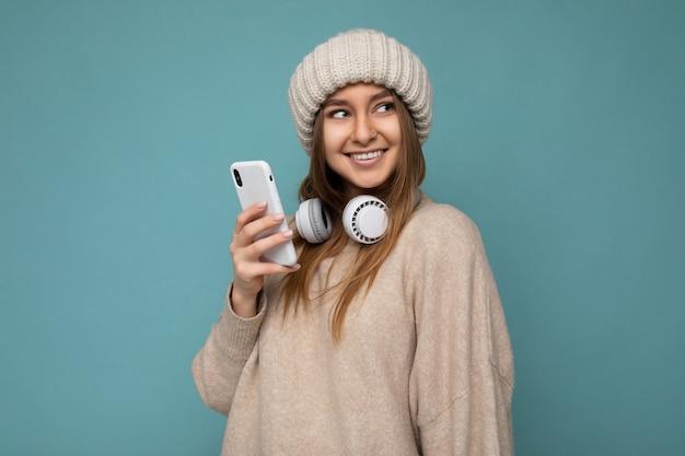 Zdjęcie przedstawiające piękną radosną uśmiechniętą młodą kobietę noszącą stylowy, swobodny strój na białym tle