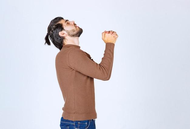 Zdjęcie przedstawiające przystojnego mężczyznę patrzącego w górę i trzymającego się za ręce hands