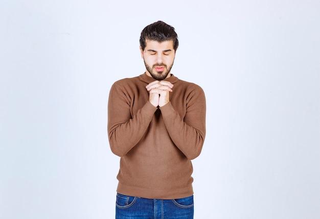 Zdjęcie przedstawiające przystojnego mężczyznę trzymającego się za ręce z zamkniętymi oczami