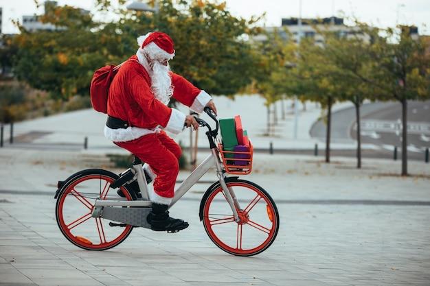 Zdjęcie przedstawiające świętego mikołaja z prezentami na rowerze i jego czerwoną walizką na plecach.