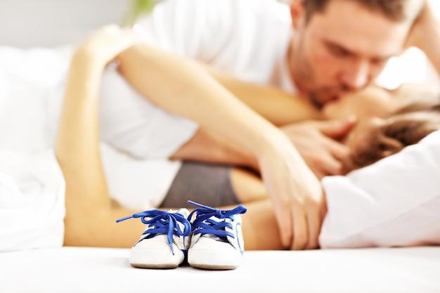 Zdjęcie przedstawiające szczęśliwą parę całującą się w łóżku i dziecięce buciki
