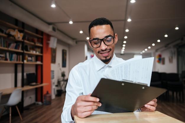 Zdjęcie przedstawiające szczęśliwego biznesmena w okularach siedzącego przy stole i patrzącego na notatnik