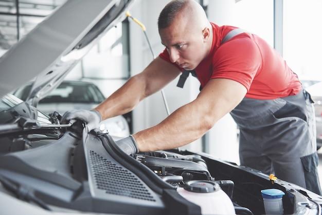 Zdjęcie przedstawiające umięśnionego pracownika serwisu samochodowego naprawiającego pojazd.
