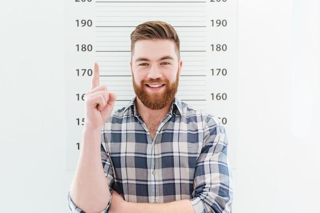 Zdjęcie przedstawiające uśmiechniętego mężczyznę wskazującego palcem w górę