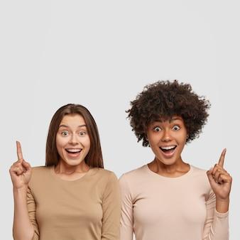 Zdjęcie przedstawiające wesołą ciemnoskórą kobietę i jej koleżankę, wskazujące palcami wskazującymi w górę