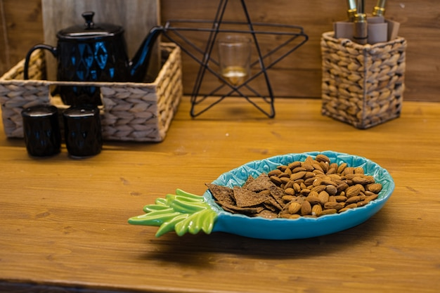 Zdjęcie przedstawiające wygodną kuchnię z brązowym stołem z niebieskim talerzem ananasowym i ciasteczkami