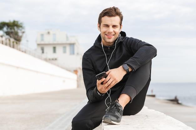 Zdjęcie przedstawiającego kaukaskiego sportowca 30-latka w czarnej odzieży sportowej, korzystającego ze słuchawek i telefonu komórkowego, siedzącego na promenadzie nad morzem