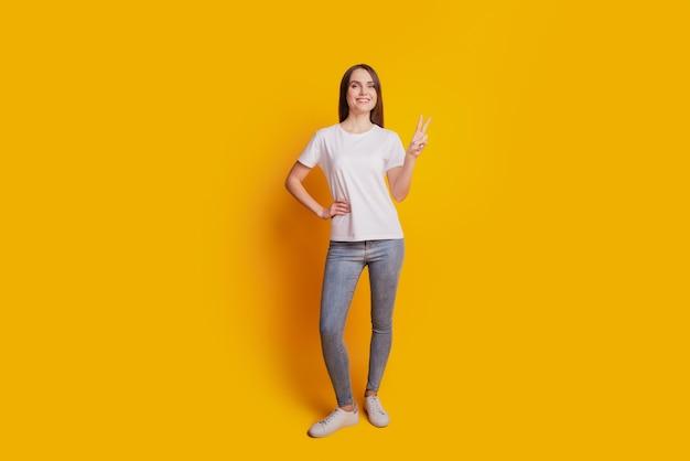 Zdjęcie przepięknej przyjaznej damy pokazuje znak v nosić białą koszulkę pozującą na żółtym tle