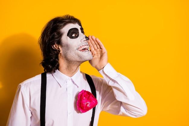 Zdjęcie przerażające nieumarłe stworzenie facet ręka usta podekscytowany nadzieję rozprzestrzenianie się plotka wygląd pusta przestrzeń nosić biała koszula róża cukier czaszka śmierć kostium szelki na białym tle żółty kolor tło