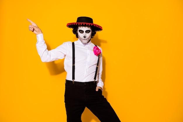 Zdjęcie przerażającego faceta bezpośredni palec pusta przestrzeń ręka kieszeń pokaż niebezpieczeństwo promocja nosić biała koszula róża śmierć kostium cukier czaszka sombrero szelki na białym tle żółty kolor tła