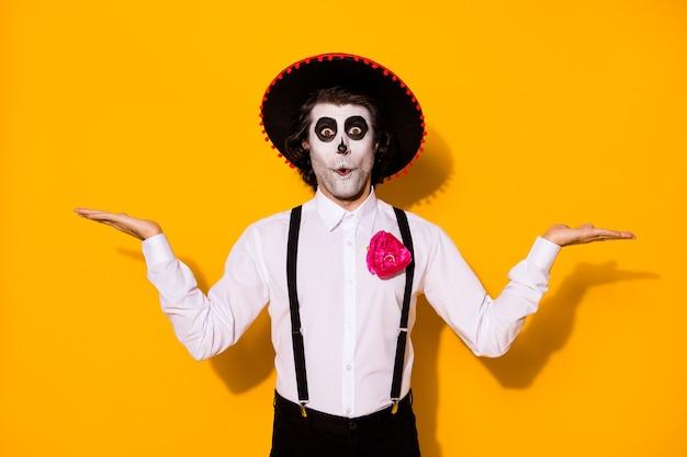 Zdjęcie przerażającego zombie faceta ręce trzymają dwie ręce pusta przestrzeń podekscytowany niespodzianka dobre opcje umarli mężczyźni noszą białą koszulę śmierć kostium cukrowa czaszka szelki na białym tle żółty kolor tła