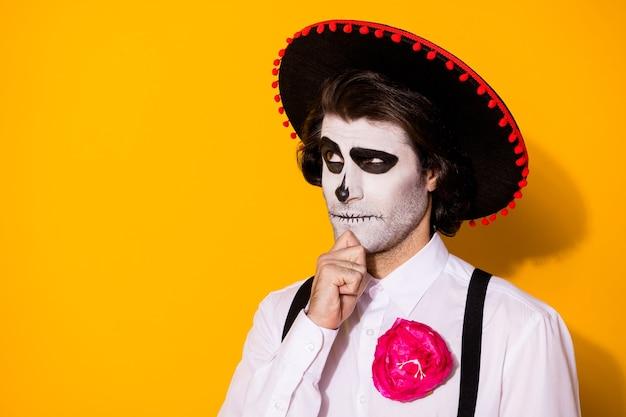 Zdjęcie przerażający niepewny zły duch facet ręka podbródek spójrz w górę pusta przestrzeń pamiętaj, kiedy umarł nosić białą koszulę kwiat śmierć kostium cukier czaszka szelki na białym tle żółty kolor tło