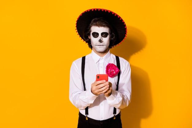 Zdjęcie przerażający straszny zombie facet ręka trzymać telefon rozmawiający duch przyjaciel sieć społecznościowa nosić biała koszula kwiat śmierć kostium cukier czaszka szelki na białym tle żółty kolor tła