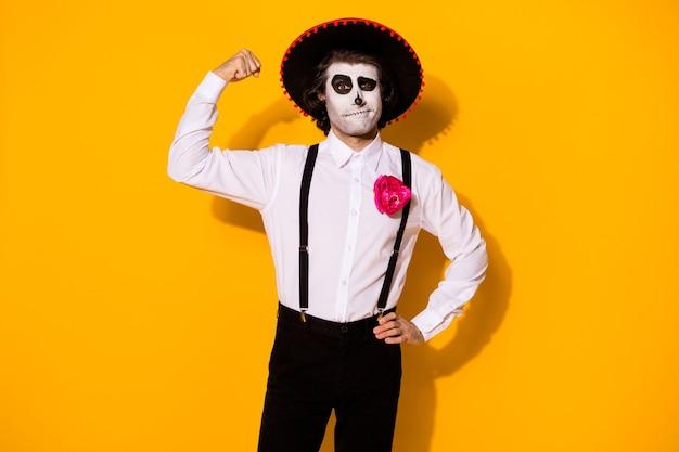 Zdjęcie przerażający toreador facet pokaż biceps ręka biodra wyzwanie szalony byk pojedynek potężny zwycięski bohater nosić białą koszulę śmierć kostium cukier czaszka szelki na białym tle żółty kolor tło