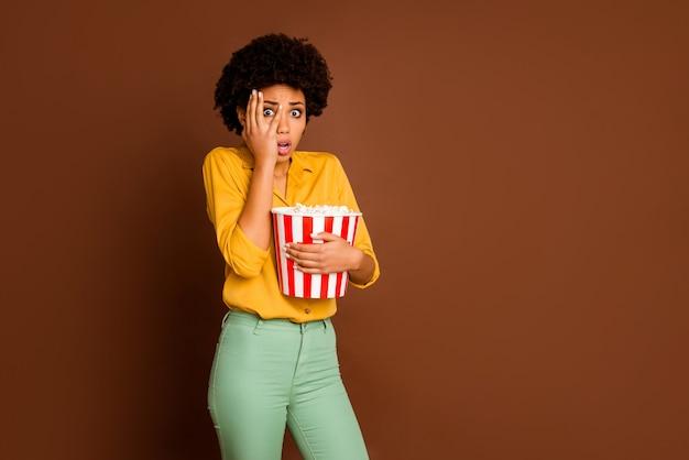 Zdjęcie przerażonej ciemnej skóry falistej pani trzymaj wiadro popcornu jedz kukurydzę oglądaj straszny film thriller ukryj oko przerażone nosić żółtą koszulę zielone spodnie na białym tle brązowy kolor
