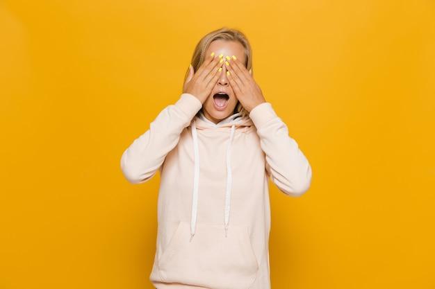 Zdjęcie przestraszonej młodej kobiety z aparatami ortodontycznymi zakrywającymi oczy, odizolowane na żółtym tle