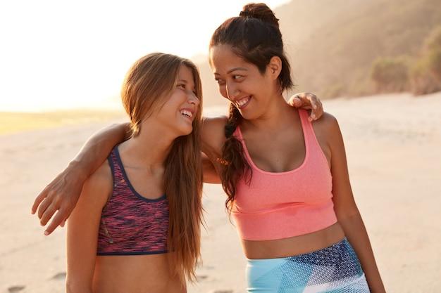Zdjęcie przyjaznych zabawnych kobiet obejmujących się podczas spaceru po plaży