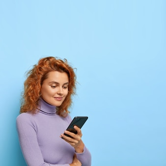 Zdjęcie przyjemnie wyglądającej rudej kobiety stoi na wpół obrócona, używa nowoczesnego smartfona, sprawdza skrzynkę e-mail, ubrana w zwykły strój, odizolowana na niebieskiej ścianie, skopiuj miejsce na reklamę