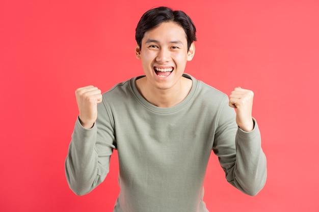 Zdjęcie przystojnego azjaty, który ręką wyraża swoje uczucia zwycięstwa