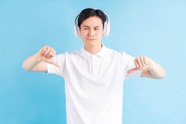 Zdjęcie przystojnego azjaty o nieprzyjemnym spojrzeniu podczas słuchania muzyki