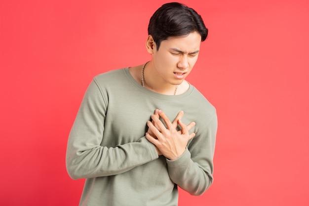 Zdjęcie przystojnego azjaty trzymającego ramiona wokół klatki piersiowej z powodu ataku serca