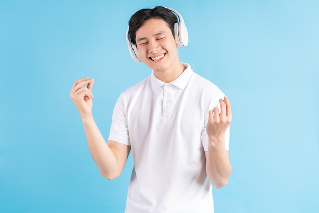 Zdjęcie przystojnego azjatyckiego chłopca słuchającego muzyki i podążającego za nią