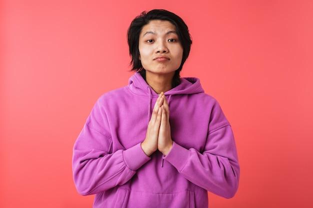 Zdjęcie przystojnego azjatyckiego faceta w bluzie trzymającego dłonie razem do modlitwy na białym tle nad czerwoną ścianą