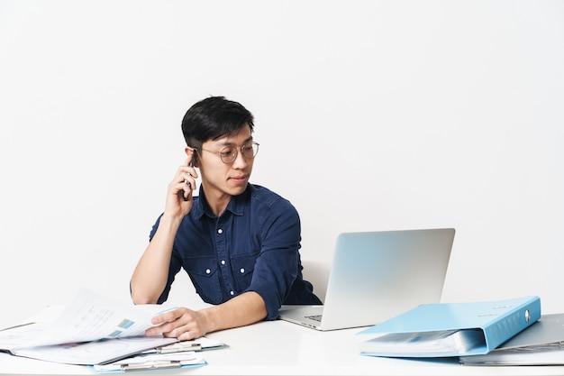 Zdjęcie przystojnego azjatyckiego mężczyzny w wieku 30 lat w okularach, siedzącego przy stole i rozmawiającego na smartfonie podczas pracy w jasnym pokoju biurowym