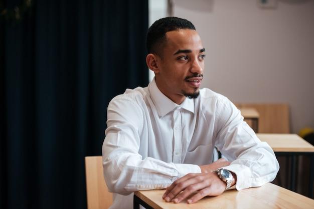 Zdjęcie przystojnego biznesmena siedzącego przy stole i patrzącego na bok