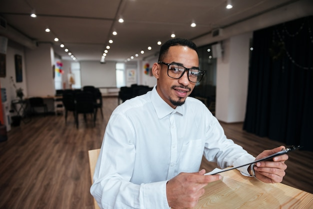 Zdjęcie przystojnego biznesmena w okularach siedzącego przy stole i patrzącego na przód