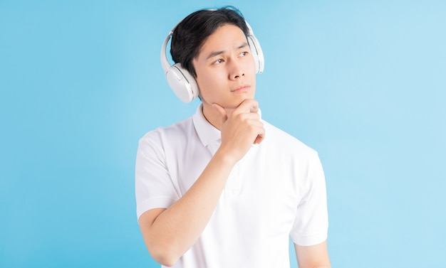 Zdjęcie przystojnego chłopca azjatyckiego słuchania muzyki i myślenia