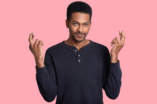 Zdjęcie przystojnego ciemnoskórego młodego człowieka z poważnym wyrazem twarzy trzyma kciuki