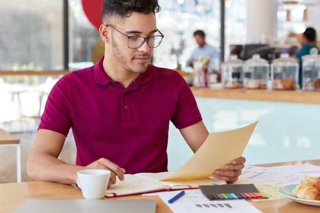 Zdjęcie przystojnego ciemnowłosego młodzieńca trzyma dokument, czyta informacje, otwiera notatnik, studiuje grafikę i diagramy, nosi swobodne ubrania, pije aromatyczną kawę, pozuje w przytulnej kawiarni