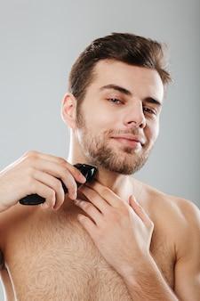 Zdjęcie przystojnego dorosłego faceta wykonującego zabiegi higieniczne i zdrowotne z goleniem włosia za pomocą trymera na szarej ścianie