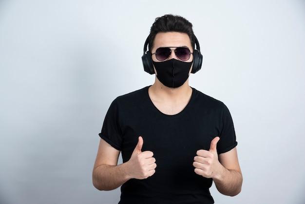 Zdjęcie przystojnego faceta w słuchawkach pokazujące kciuki do góry.