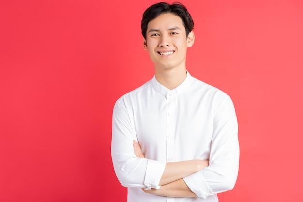 Zdjęcie przystojnego mężczyzny azjatyckiego stojącego z rękami skrzyżowanymi na czerwonej ścianie