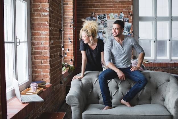 Zdjęcie przystojnego mężczyzny i jasnowłosej kobiety w pokoju z ceglanymi ścianami i sofą pośrodku