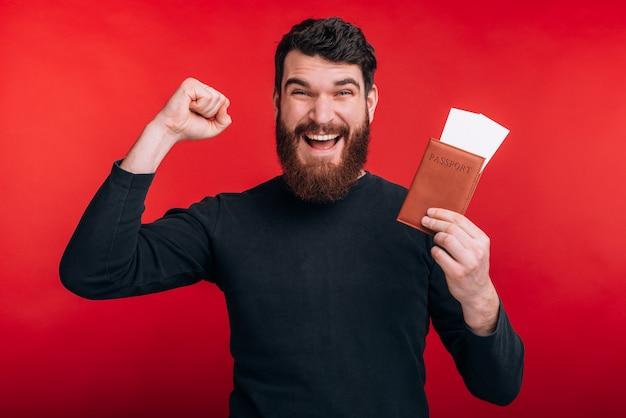 Zdjęcie przystojnego mężczyzny jest gotowe do podróży i posiadania paszportu z biletami lotniczymi