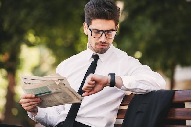 Zdjęcie przystojnego mężczyzny w garniturze, czytającego gazetę na ławce w zielonym parku i patrząc na zegarek