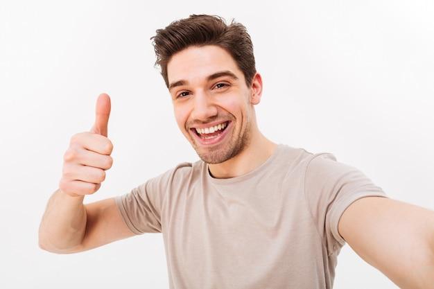 Zdjęcie przystojnego mężczyzny w swobodnej koszulce i włosiu na twarzy, uśmiechając się do kamery z kciukiem do góry podczas robienia selfie, na białym tle nad białą ścianą